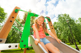 image of chute  - Funny girl on playground chute ready to slide and holding the sides of metallic chute - JPG