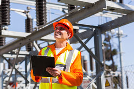 stock photo of substation  - happy middle aged electrical engineer with clipboard in substation - JPG