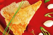 food : cheese casserole piece over red plate served with chives , tomatoes and hot peppers isolated over white