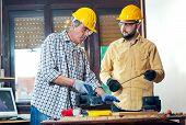 Home improvement - handyman sanding wooden floor in workshop, selective focus