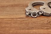 Steel Handcuffs On Wooden Table