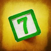 stock photo of number 7  - Lucky number seven on a green and white toy wooden building block on a yellow background - JPG
