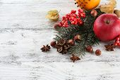 Fruits with spices, rowan, and Christmas pine sprig on color wooden background