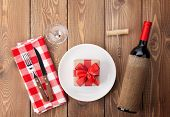 Table setting with gift box on plate, wine glass and red wine bottle. View from above over rustic wooden table background