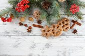 Cookies with spices, rowan and Christmas pine sprigs on color wooden background