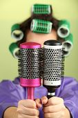 Girl in hair curlers  holding hair combs on colorful background