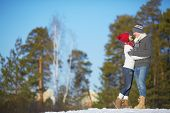 Affectionate couple in knitted winterwear spending leisure outdoors