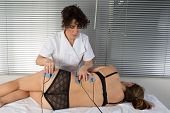 image of hernia  - woman is doing massage of electrostimulator for the spine - JPG