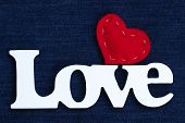 Love text with red fabric heart on denim background