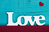 Love text and red heart on blue wood background