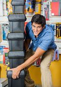 Portrait of smiling young man carrying stacked toolboxes in hardware store