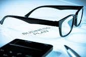 Business Plan Words Near Glasses, Pen And Calculator, Business Concept