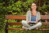 Smiling student sitting on bench listening music with mobile phone and holding book in park at school
