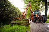 mowing grass shoulder along road in public space  with big orange tractor mower
