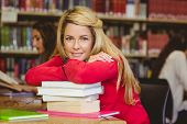 Smiling mature student leaning on a stack of books in library