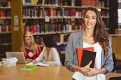 Pretty student holding books with classmates behind her in library