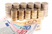 Euro banknotes and coins organized in columns isolated on white background