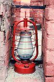 Kerosene lamp on ruined brick wall background