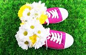 Beautiful gumshoes with flowers inside on green grass background