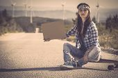 stock photo of swag  - Beautiful young woman sitting over a skateboard - JPG
