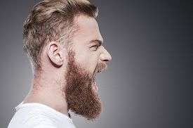 pic of shout  - Side view of furious young bearded man shouting while standing against grey background - JPG