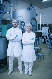 stock photo of food plant  - Food technicians smiling at camera in a food processing plant - JPG