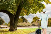 picture of air hostess  - Pretty air hostess leaning on suitcase against scenic backdrop - JPG