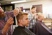 stock photo of facial piercings  - Male Barber Giving Client Haircut In Shop - JPG