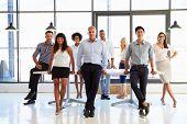 image of coworkers  - Coworkers posing to camera in meeting room - JPG