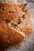 pic of sponge-cake  - Traditionally home baked sultana or dried fruit light sponge cake with a slice removed - JPG