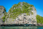 foto of phi phi  - Cliff and the clear sea with a boat near Phi Phi island in south of Thailand - JPG