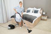 foto of housekeeper  - Female Housekeeper Cleaning Rug With Vacuum Cleaner In Hotel Room - JPG