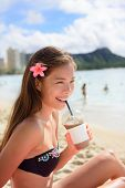 stock photo of woman bikini  - Beach woman drinking iced coffee cappuccino drink enjoying beach lifestyle smiling happy on Waikiki - JPG
