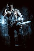 picture of man chainsaw  - Handsome muscular man with a chainsaw over dark grunge background - JPG
