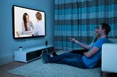 stock photo of watching movie  - Couple With Remote Control Watching Movie At Home - JPG