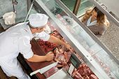image of slaughterhouse  - High angle view of butcher selling meat to customer at display cabinet in butchery - JPG