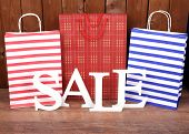 stock photo of year end sale  - Sale with bags on wooden background - JPG