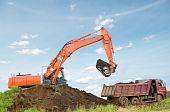 image of dumper  - Heavy excavator loading dumper truck with sand in sandpit over blue sky - JPG