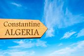 stock photo of algeria  - Wooden arrow sign pointing destination CONSTANTINE ALGERIA against clear blue sky with copy space available - JPG