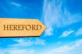 foto of hereford  - Wooden arrow sign pointing destination HEREFORD ENGLAND against clear blue sky with copy space available - JPG