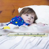 image of high fever  - Mercury thermometer showing high temperature and a little sick girl in bed - JPG