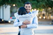 foto of enamored  - Closeup portrait back view young couple in blue shirt hugging smiling isolated outdoors outside background - JPG