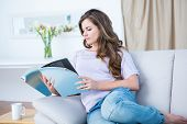 stock photo of peaceful  - Peaceful woman reading a magazine at home in the living room - JPG