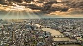 stock photo of train-wheel  - Overhead view of the skyline of London in England with the river Thames against a moody and cloudy sky with the suns rays breaking though - JPG