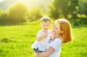 picture of mother baby nature  - happy family on nature outdoors mother and baby daughter on the green meadow - JPG