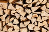 stock photo of firewood  - Background of chopped firewood stacked up on top of each other in a pile - JPG