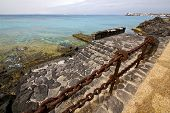 stock photo of stelles  - pier rusty chain water boat yacht coastline and summer in lanzarote spain - JPG