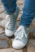 picture of paving stone  - woman retro tennis shoes and blue jeans with stone paving in background - JPG