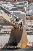 stock photo of paving stone  - Excavator bucket on construction site stone paving pallets in background - JPG