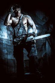 foto of man chainsaw  - Handsome muscular man with a chainsaw over dark grunge background - JPG